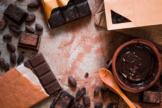 Chocolate bar, cocoa beans, and chocolate cream on table Free Photo