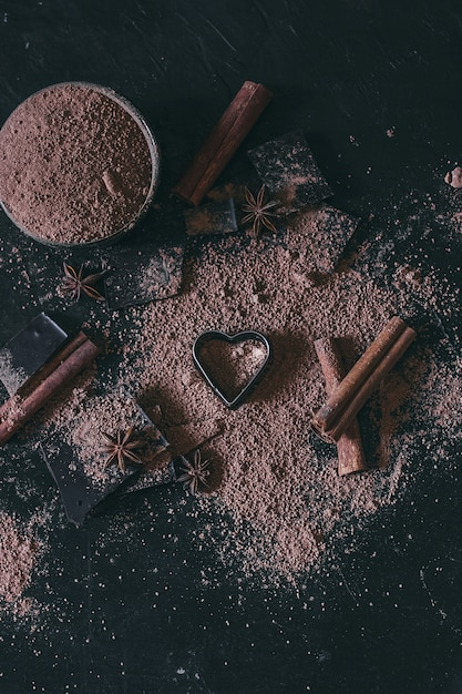 Chocolate bar pieces with cocoa powder and heart shape on dark Premium Photo