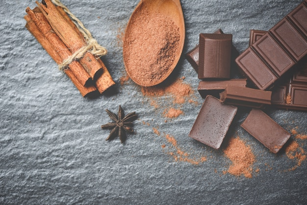 Chocolate bar and spice on dark background powder chocolate on spoon and pieces candy sweet dessert for snack Premium Photo