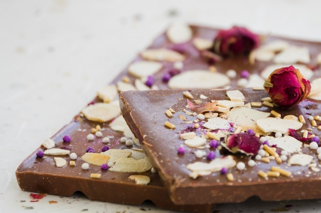 Chocolate bar with dried fruits and rose on white backdrop Free Photo
