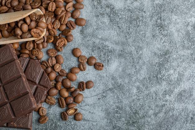 灰色のコーヒー豆とチョコレートバー。 無料写真