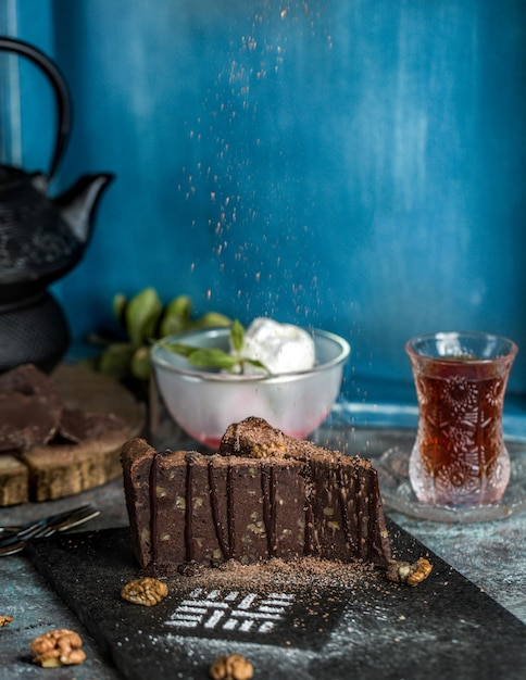 Chocolate brownie cake with ice cream balls and a glass of tea Free Photo