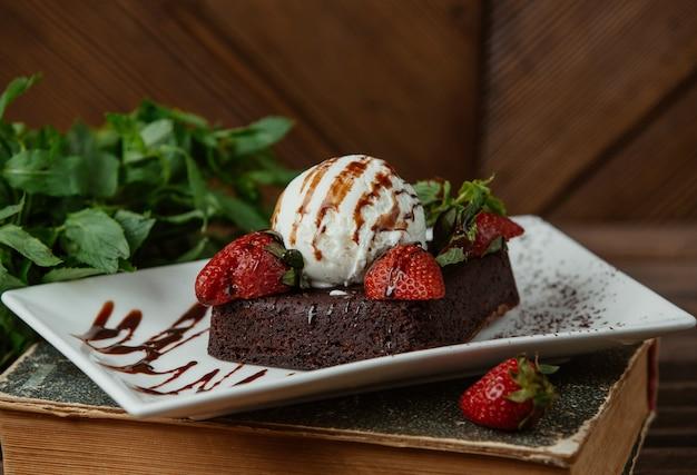 Chocolate brownie served with vanilla icecream ball and strawberries Free Photo