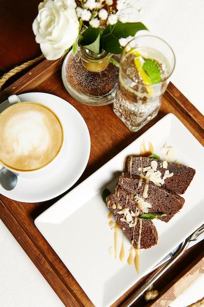 チョコレートブラウニークリーム、カプチーノ1杯、レモン1杯の水とトレイ。ヘルシーな朝食 Premium写真