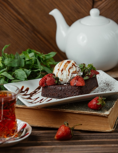 Chocolate brownie with icecream ball and strawberries , and a glass of tea Free Photo