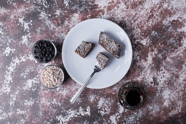 Chocolate brownies served with a glass of tea, top view Free Photo