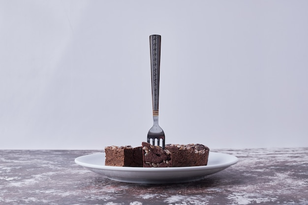 Chocolate brownies in a white plate with a fork on it on grey background Free Photo