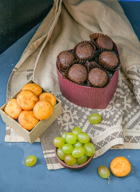 Chocolate buns and cookies with grapes. Free Photo