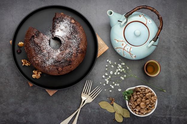 Chocolate cake on a black plate with a tea kettle Free Photo