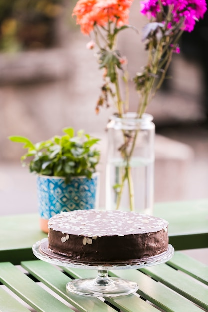 Chocolate cake decorated with almond slices on cake stand over table Free Photo