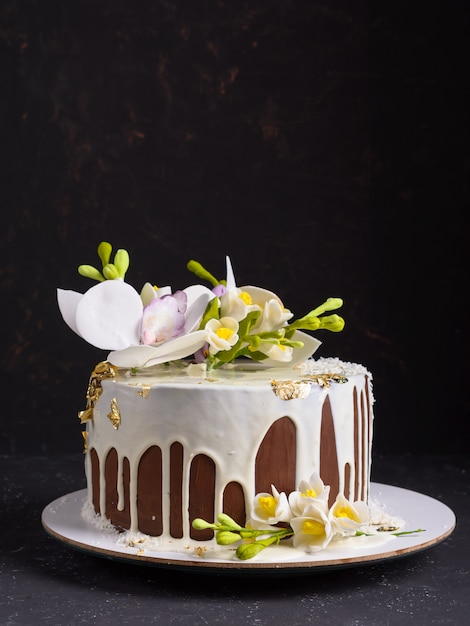Chocolate cake decorated with flowers and poured white icing. copyspace Premium Photo