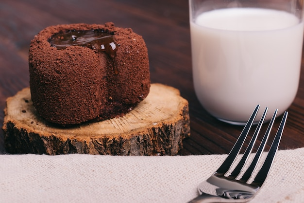 Chocolate cake and glass of milk on a brown table, fork on the tablecloth Premium Photo