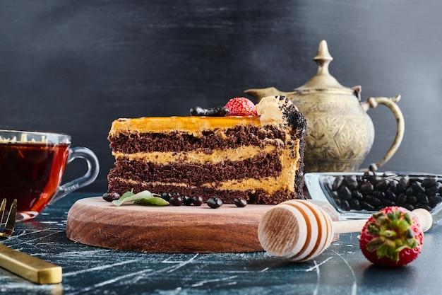 Шоколадный торт подается со стаканом чая. Бесплатные Фотографии