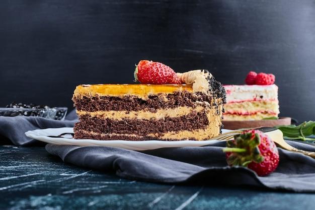 青い背景にベリーを添えたチョコレートケーキ。 無料写真