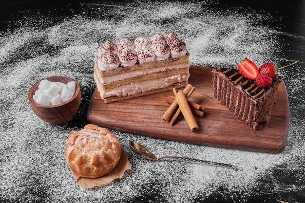 Fetta di torta al cioccolato con tiramisù su un piatto di legno. Foto Gratuite