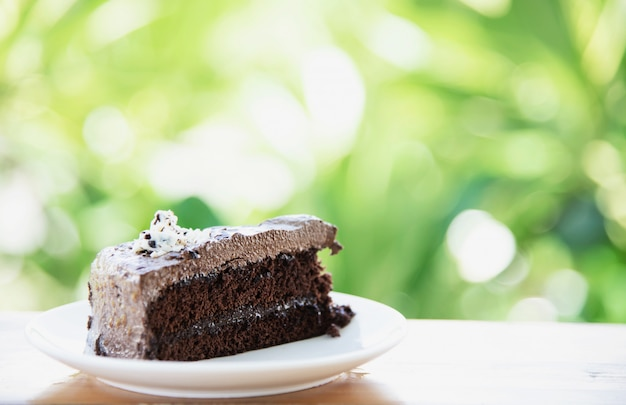 Chocolate cake on table with green garden - relax with bakery and nature concept Free Photo
