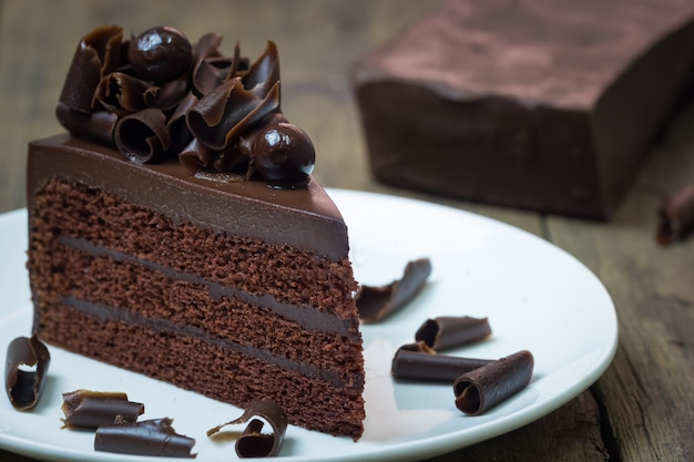 Chocolate cake topping with chocolate curl on wood background Premium Photo