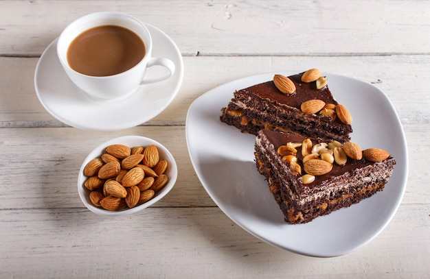 Chocolate cake with caramel, peanuts and almonds on a white wooden surface. Premium Photo