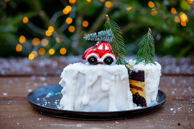 Chocolate cake with cream on wooden table with spruce Premium Photo