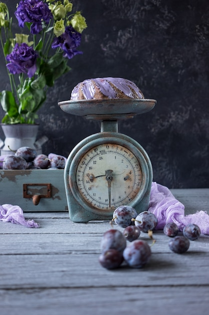 Chocolate cake with lilac flowers and plums in a vintage wooden box Premium Photo