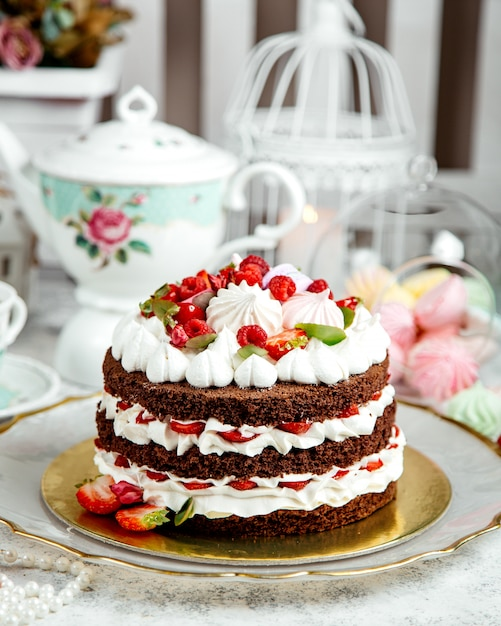 Chocolate cake with whipped cream and fruits Free Photo