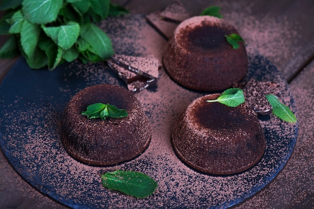 Chocolate cakes with mint. brownies with dark chocolate and mint leaves on dark background. Premium Photo