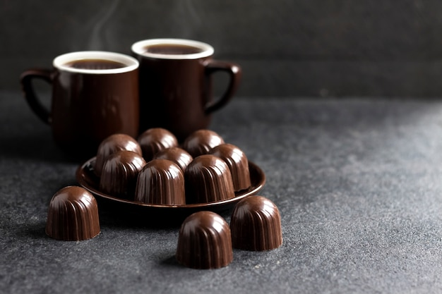 Chocolate candies on a plate and two cups of coffee on black surface Premium Photo