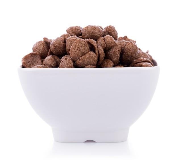 Chocolate cereals in white bowl on white background. cornflakes Premium Photo