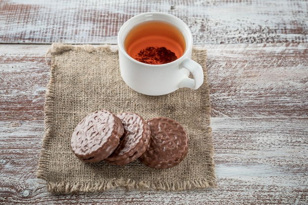 Chocolate chip cookies and a mug of tea on white wooden table. Premium Photo