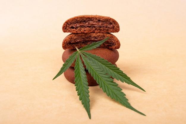 緑の葉のマリファナの植物とチョコレートチップクッキー。大麻のお菓子、クッキーのスタック。 Premium写真