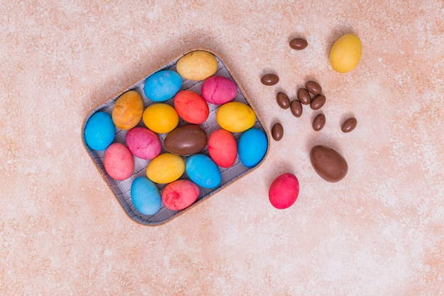 Chocolate and colorful easter eggs in box Free Photo