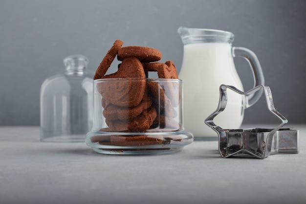 Шоколадное печенье и банка молока на синем фоне. Бесплатные Фотографии