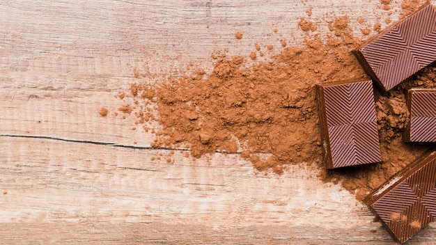 Chocolate and crumbs on wooden table Free Photo