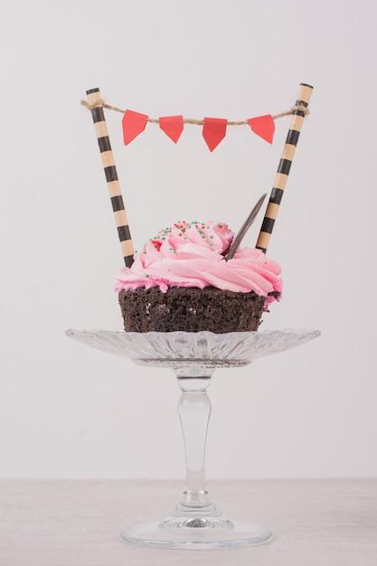 Cupcake al cioccolato con glassa e spruzzatori su vetro. Foto Gratuite