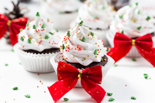 Chocolate cupcakes decorated white cream and fir trees on a white plate. christmas sweets. new year dessert Premium Photo