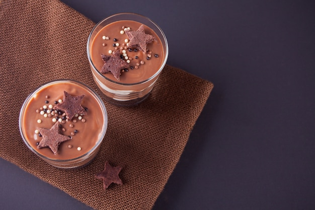 Chocolate dessert in glass jars on a table with wooden spoon. top view. Premium Photo