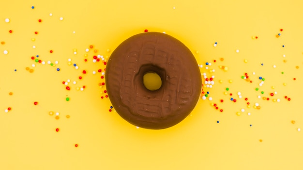 Chocolate donut with colorful sprinkles on yellow background Free Photo