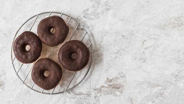 大理石のテクスチャ付きの背景の上に金属製のラックにチョコレートドーナツ 無料写真