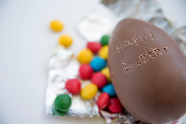 Chocolate egg with happy easter title and candies on foil Free Photo