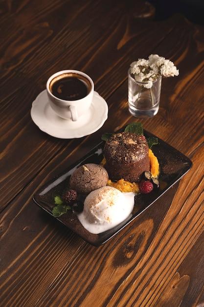 一杯のコーヒーの横にある木製のレストランのテーブルにアイスクリームとベリーとチョコレートフォンダン Premium写真