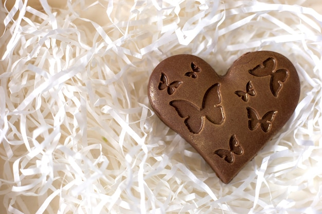 Chocolate heart with butterflies over white paper ribbons Premium Photo