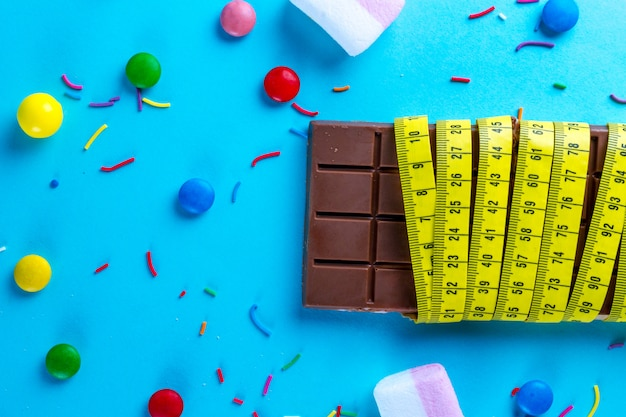 Chocolate is wrapped in a measuring tape with different sweets Premium Photo