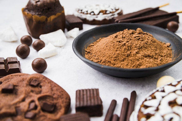 Chocolate items with cocoa powder in bowl Free Photo