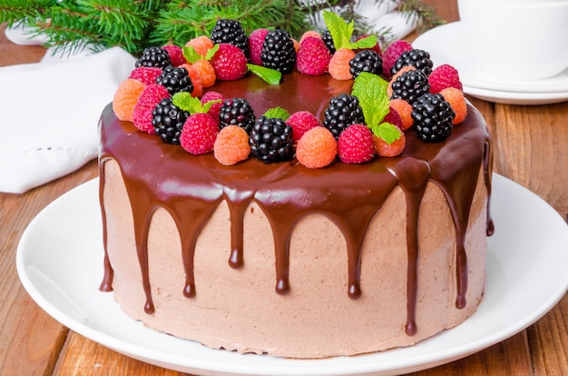 Chocolate layer cake with cherry filling and fresh berries on top of the new year and christmas Premium Photo