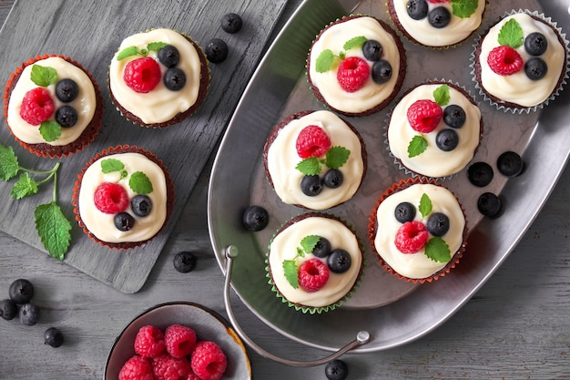 Chocolate muffins or cupcakes with whipped cream and berries in metal dishes Premium Photo