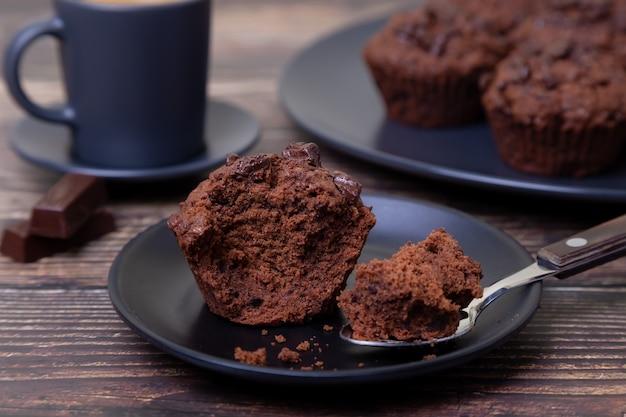 검정 잉크 판에 초콜릿 머핀입니다. 수제 베이킹. 배경에는 커피 한 잔과 머핀이 담긴 접시가 있습니다. 나무 배경입니다. 선택적 초점을 닫습니다. 프리미엄 사진