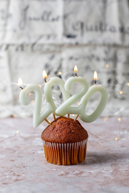 Chocolate muffins on top 2020 candles on light brown surface Free Photo