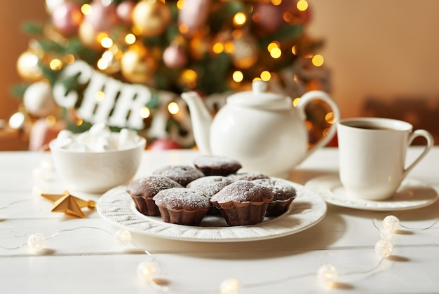 Chocolate muffins with tea  of christmas tree. xmas . greeting card and calendar template. christmas decoration. holiday dinner, sweet treats for kids. Premium Photo