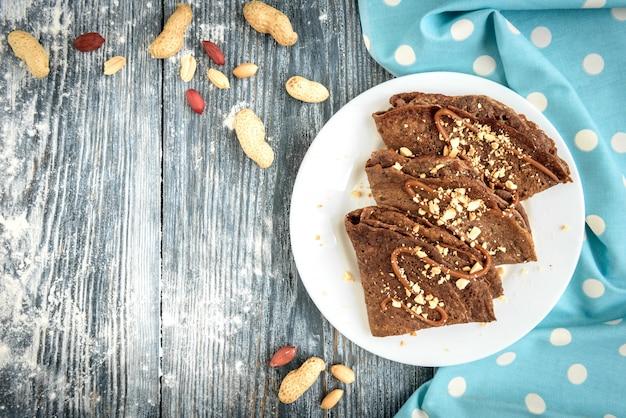 Шоколадные овсяные блинчики с карамелью и орехами на серый деревянный стол. Premium Фотографии