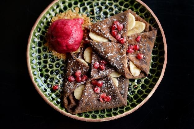 Chocolate pancake with bananas, pomegranate and sorbet Premium Photo